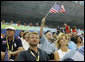 President George W. Bush, accompanied by Mrs. Laura Bush, waves an American flag as he cheers for the U.S. Olympic swimming team Monday, Aug. 11, 2008, in the National Aquatic Center at the 2008 Summer Olympic Games in Beijing. White House photo by Eric Draper