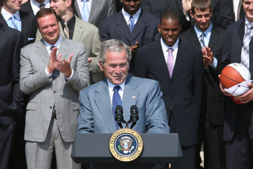 """President George W. Bush acknowledges the applause as he greets the University of Kansas Jayhawks Tuesday, June 3, 2008, to the Rose Garden. President Bush told the 2008 NCAA Men's Basketball champs, """"I want to congratulate this team. You brought new glory to one of our nation's most storied basketball programs, and you gave your fans all across America one more reason to chant: Rock Chalk, Jayhawk!"""" White House photo by Joyce N. Boghosian"""