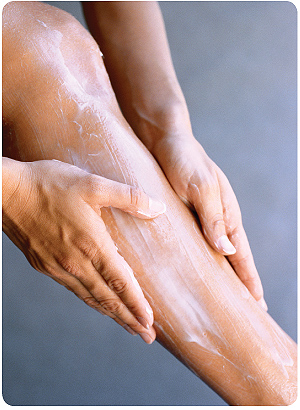 photo close up of woman spreading cream on her leg