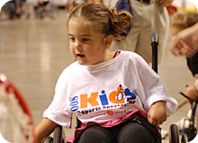 Image of a very young girl smiling while she plays wheelchair tennis. Link to full story