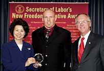 Secretary Chao (left) presents a New Freedom Initiative Award to Michael John Maslowski (center) of the Kansas City Chiefs as Assistant Secretary of Labor Roy Grizzard (right) looks on