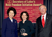 Secretary of Labor Elaine L. Chao (L) and Assistant Secretary of Labor for Disability Employment Policy Roy Grizzard (R) present a 2004 Secretary of Labor's New Freedom Initiative Award to Pamela Passman (center) Deputy General Counsel Microsoft Corporation
