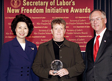 Secretary of Labor Elaine L. Chao (L) and Assistant Secretary of Labor for Disability Employment Policy Roy Grizzard (R) present a 2004 Secretary of Labor's New Freedom Initiative Award to J. Erin Riehle Co-Director, Project SEARCH