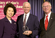 Secretary of Labor Elaine L. Chao (L) and Assistant Secretary of Labor for Disability Employment Policy Roy Grizzard (R) present a 2004 Secretary of Labor's New Freedom Initiative Award to Richard E. Marriott of the Marriott Foundation