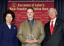 Secretary of Labor Elaine L. Chao (L) and Assistant Secretary of Labor for Disability Employment Policy Roy Grizzard (R) present a 2004 Secretary of Labor's New Freedom Initiative Award to Jason Korte (center) Co-Owner A & F Wood Products, Inc.