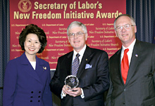 Secretary of Labor Elaine L. Chao (L) and Assistant Secretary of Labor for Disability Employment Policy Roy Grizzard (R) present a 2004 Secretary of Labor's New Freedom Initiative Award to Victor P. Manning President & Executive Director MBNA Foundation