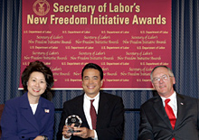 Secretary of Labor Elaine L. Chao (L) and Assistant Secretary of Labor for Disability Employment Policy Roy Grizzard (R) present a 2004 Secretary of Labor's New Freedom Initiative Award to Michael Takemura(c) Director, HP Accessibility Program Office