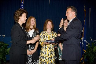 Secretary Elaine L. Chao administers the Oath of Office to Neil Romano