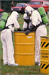 people in protective suits handling toxic material