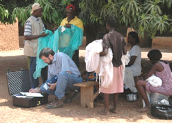 Dr. Steve Smith, CDC, uses a portable X-ray fluorescence analyzer to measure the content of insecticide in an insecticide-treated bednet in rural Ghana.