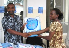 Ali Khamis Abbas presents a long-lasting insecticide-treated net to Consolata John.