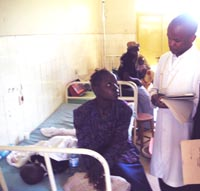 A clinician examines a child hospitalized with a fever possibly caused by malaria.