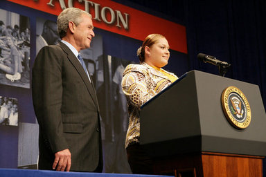 President George W. Bush listens as Edith Espinoza, Administrative Assistant, Chicano Federation, introduces him at the Office of Faith-Based and Community Initiatives National Conference Thursday, June 26, 2008, in Washington, D.C. The President opens his remarks, 'How beautiful was that? From being a homeless mother of two to introducing the President of the United States. There has to be a higher power. I love being with members of the armies of compassion, foot soldiers in helping make America a more hopeful place. Every day you mend broken hearts with love. You mend broken lives with hope. And you mend broken communities with countless acts of extraordinary kindness.' White House photo by Chris Greenberg.
