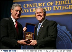 President George W. Bush is presented with an honorary FBI Special Agent credential by FBI Director Robert Mueller Thursday, Oct. 30, 2008, at the graduation ceremony for FBI special agents in Quantico, Va. White House photo by Joyce N. Boghosian