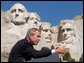 """President George W. Bush discusses the security of America at Mount Rushmore in South Dakota Thursday, Aug. 15 """"More and more people understand that being a patriot is more than just putting your hand over your heart and saying the Pledge of Allegiance to a nation under God. (Applause.) They're saying -- more and more people understand that serving something greater than yourself in life is a part of being a complete American,"""" said the President in his remarks."""