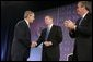 President George W. Bush is congratulated by Attorney General John Ashcroft and Florida Governor Jeb Bush after making remarks at the National Training Conference on Combating Human Trafficking in Tampa, Florida on Friday July 16, 2004.  White House photo by Paul Morse