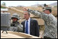 President George W. Bush watches as a soldier operates technical field equipment, joined by U.S. Army Captain Pat Armstrong, right, during President Bush's visit to the U.S. Army National Training Center Wednesday, April 4, 2007, at Fort Irwin, Calif.  White House photo by Eric Draper