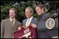 President George W. Bush accepts a team jersey from the NCAA Championship hockey team from the University of Minnesota on the South Lawn Tuesday, May 21. Also attending were University of Connecticut's women's basketball team, University of Maryland's men's basketball team, and University of Minnesota's women's hockey team.