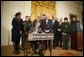 President George W. Bush is joined by legislators, cabinet members and law enforcement officials, Tuesday, Oct. 18, 2005 in the East Room of the White House, as he signs the Homeland Security Appropriations Act for fiscal year 2006.  White House photo by Paul Morse