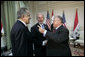 President George W. Bush shakes hands with Iraqi President Jalal Talabani, right, during his visit Tuesday, June 13, 2006, to the U.S. Embassy in Baghdad. With them is U.S. Ambassador to Iraq Zalmay Khalilzad.  White House photo by Eric Draper
