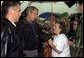Listening to the story of how a tornado swept through their town, President George W. Bush meets one-on-one with residents during his walking tour of Pierce City, Mo., Tuesday, May 13, 2003.  White House photo by Susan Sterner