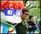 "A United States Marine and her son stand for pictures with Chuckie, a character from the cartoon, ""Rugrats,"" during the White House Easter Egg Roll Monday, April 21, 2003. More than 30 children's characters wandered through the South Lawn during the day's festivities, including Clifford the Big Red Dog, Winnie the Pooh and the Berenstain Bears."