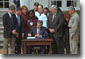 "President George W. Bush signs the Job Creation and Worker Assistance Act of 2002 during a live radio address in the Rose Garden March 9, 2002. On hand for the signing were Senators Trent Lott (far left) and Tom Daschle (second from left) and Speaker of the House Dennis Hastert (standing to right of the President). ""We're seeing some encouraging signs in the economy, but we can't stand by and simply hope for continued recovery,"" said President Bush. ""We must work for it."" White House photo by Eric Draper."