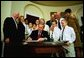 President George W. Bush signs the Adoption Promotion Act of 2003 in the Roosevelt Room December 2, 2003. Pictured with the President are the Chris and Diana Martin family. Their children are Katrina, 13, Ashley, 12, T.J., 11, Kyle, 10, Travis, 10, Dakota, 8, and Terrance, 7. Also pictured are Congressman James Oberstar, far left, Senator Mary Landrieu, and at back right, Congressman Dave Camp.  White House photo by Eric Draper