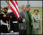 President George W. Bush and Mrs. Laura Bush stand with President Hamid Karzai of Afghanistan during an arrival ceremony at Camp David, Sunday, August 5, 2007. White House photo by Eric Draper