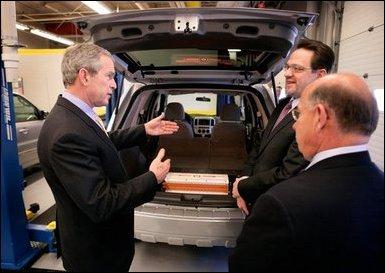 El Presidente George W. Bush examina un vehículo operado con baterías de ión de litio durante una gira el lunes, 20 de febrero de 2006 con el CEO de Johnson Controls, John Barth, derecha, y el empleado Mike Andrew en el Centro Tecnológico de Baterías de Johnson Controls en Glendale, Wisconsin. Foto por Eric Draper de la Casa Blanca