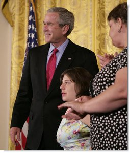 """President George W. Bush embraces stem cell patient Kaitlyne McNamara following his address on the reasons he vetoed S.5, the """"Stem Cell Research Enhancement Act of 2007,"""" in the East Room of the White House Wednesday, June 20, 2007. McNamara was born with spina bifida, a disease that damaged her bladder, her doctors isolated healthy stem cells in a piece of her own bladder and used them to grow her a new bladder.  White House photo by Eric Draper"""