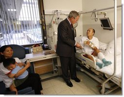 President George W. Bush visits with U.S. Army Sgt. Pengchun Pech of Lynne, Mass., Tuesday, Sept. 9, 2008, at Walter Reed Army Medical Center, where the soldier is recovering from wounds received during Operation Iraqi Freedom. Looking on is his wife, Leakhenavodey Pech, and 22-month-old son, Tommy, sit nearby. White House photo by Eric Draper