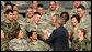 President George W. Bush greets military personnel on stage Monday, Aug. 4, 2008, at Eielson Air Force Base during a stop in Alaska en route to South Korea. White House photo by Chris Greenberg