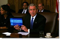 """President George W. Bush holds up a computer with the E-Budget for the cameras during a Cabinet meeting Monday, Feb. 4, 2008. Later, the President said, """"I submitted the budget today to Congress -- it's on a laptop notebook, an e-budget. It saves paper, saves trees, saves money. I think it's the first budget submitted electronically. And it's a good budget. It's a budget that achieves some important objectives. One, it understands our top priority is to defend our country, so we fund our military, as well as fund the homeland security. Secondly, the budget keeps our economy growing."""" White House photo by Joyce N. Boghosian"""
