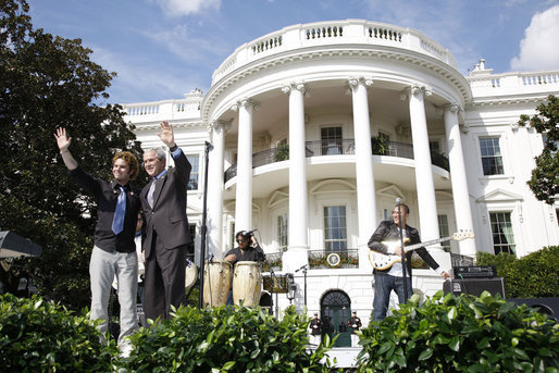 President George W. Bush is joined by Colombian musician Andres Cabas as they wave to invited guests, following Cabas and his band's performance Thursday, Oct. 9, 2008 on the South Lawn of the White House, during the celebration of Hispanic Heritage Month. White House photo by Eric Draper