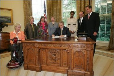 President George W. Bush signs an executive order for individuals with disabilities in emergency preparedness Thursday, July 22, 2004 in the Oval Office. White House photo by Eric Draper