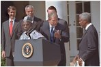 President George W. Bush welcomes UN Secretary General Kofi Annan to the podium after his announcement of Presidential HIV/AIDS Trust Fund Initiative as Nigerian President Olusegun Obsanjo looks on at left in the Rose Garden, Friday, May 11, 2001.