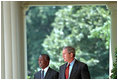 President George W. Bush and President Thabo Mbeki of South Africa walk along the colonnade to a joint press conference in the Rose Garden June 26, 2001. President Bush and President Mbeki agree that economic freedom and political freedom must go hand-in-hand to sustain peace and security.