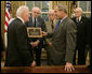 President George W. Bush is presented with a plaque at his meeting with members of the Supreme Headquarters Allied Expeditionary Force/Headquarters European Theater of Operations U.S. Army Veterans Association Friday, Oct. 6, 2006, in the Oval Office at White House. The group was organized in 1985 as a way to pay tribute to the memory of their supreme commander, Dwight D. Eisenhower, and their visit to the White House marks their 21st and final reunion gathering. White House photo by Paul Morse