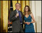 President George W. Bush joins singer Ana Cristina on stage to thank her and guitarist Marco Linares for their performance Friday, Oct. 6, 2006, in the East Room of the White House, in celebration of Hispanic Heritage Month. White House photo by Paul Morse