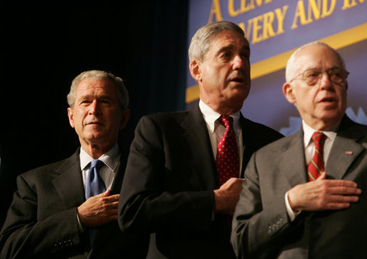 President George W. Bush joins FBI Director Robert Mueller and U.S. Attorney General Michael Mukasey during the playing of the national anthem Thursday, Oct. 30, 2008, at the graduation ceremomy for FBI special agents in Quantico, Va. White House photo by Joyce N. Boghosian