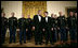 President George W. Bush and President Nicolas Sarkozy of France stand on stage with the Army Chorus in the East Room of the White House Tuesday, Nov. 6, 2007, following the after-dinner performance by the 22-member group.