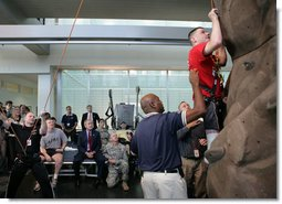 President George W. Bush, left, watches as double amputee Lance Cpl. Matt Bradford, who is also blind, climbs a wall, during President Bush's visit Thursday, Nov. 8, 2007 to the physical therapy and training area for wounded soldiers at the Center for The Intrepid at the Brooke Army Medical Center in San Antonio, Texas. White House photo by Eric Draper