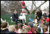 """Hall of Fame football player Troy Aikman reads """"One Fish, 2 Fish, Red Fish, Blue Fish"""" for children at the reading nook at the 20008 White House Easter Egg Roll, Monday, March 24, 2008."""