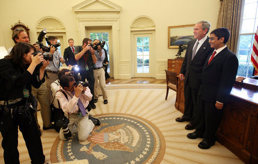 """President George W. Bush stands with Sameer Mishra, 14, of Lafayette, Ind., during his visit Wednesday, Aug. 13, 2008, to the Oval Office of the White House. The teen was named the 2008 Scripps National Spelling Bee Champion in the 16th round after correctly spelling the word """"guerdon,"""" meaning a reward or recompense). White House photo by Joyce N. Boghosian"""