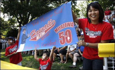 Tee Ball All-Star Joshua Miyazawa, age 5, gets a boost from his Hawaiian fan club as he plays on the South Lawn of the White House on July 16, 2008. The banner also holds a greeting for President George W. Bush, who watched the demonstration of teamwork and discipline from a nearby bleachers with Mrs. Laura Bush and the families of the children attending. One child represented each state and the District of Columbia and the teams were divided into Western, Central, Southern and Eastern teams, with Joshua playing on the Western Team.