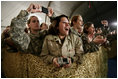 U.S. and Coalition troops cheer and take photos Wednesday, March 1, 2006, during an appearance by President George W. Bush and Mrs. Laura Bush at Bagram Air Base in Afghanistan.
