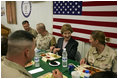 Laura Bush laughs with troops as they eat dinner in the Dragon Chow Dining Hall at Bagram Air Base in Kabul, Afghanistan, Wednesday, March 30, 2005.