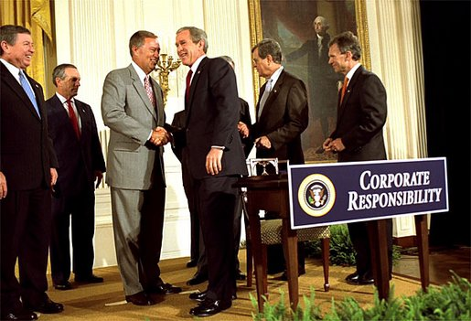 """President George W. Bush shakes hands with Congressman Mike Oxley, R-OH, during the signing of the ceremony of the Sarbanes-Oxley Act in the East Room, July 30. """"This new law sends very clear messages that all concerned must heed. This law says to every dishonest corporate leader: you will be exposed and punished; the era of low standards and false profits is over; no boardroom in America is above or beyond the law,"""" said the President in his remarks."""