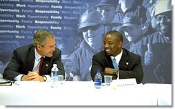 President George W. Bush talks with Patrick Patterson during a roundtable discussion on welfare reform in Charleston, S.C., Monday, July 29.
